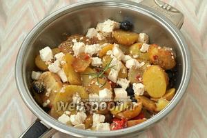 В сковороду вернуть весь обжаренный картофель, добавить Фету или брынзу, а также маслины. Посолить и поперчить, добавить орегано.