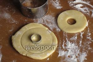 Тесто раскатать в пласт толщиной 7 мм. Формочкой вырезать кружочки диаметром 8 см. В середине каждого кольца сделать отверстие диаметром 2 см.