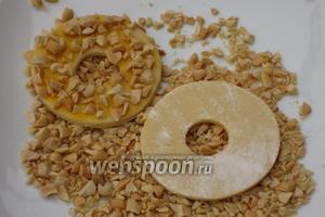 Каждое кольцо обвалять в орехах и выложить на противень с пергаментом.