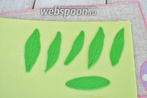 Вспомним уроки лепки в детском саду. Раскатаем мастику и вырежем листики для тюльпанов. Зубочисткой нанесём прожилки на листики и отложим в сторону.