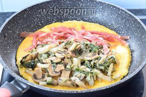 Кладём на омлет 1/2 порции овощей и нарезанного мяса.
