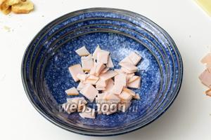 Пока чеснок проваривается, нарежем мелко ветчину и сыр. Мясо кладём в тарелки.