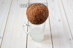 Слейте кокосовую воду, проковыряв 1 из «глазков» ореха ножом. В моём кокосе было ровно 100 мл.