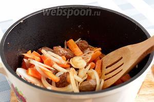 В казан к мясу добавить лук и морковь. Всё нарезается довольно крупно. В процессе приготовления лук полностью растворяется, а морковь остаётся кусочками. Обжарить до мягкости лука и моркови.