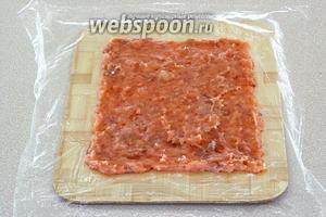 На пищевую плёнку выложить фарш слоем толщиной 5 мм.