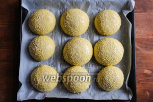 Расстоявшиеся булочки увеличатся в объёме в 2 раза. Смажьте их смесью желтка и 1 ст. л. молока, и присыпьте кунжутом.