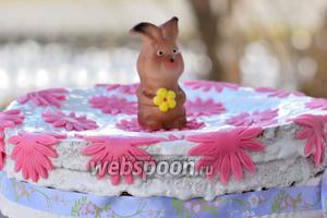 На торт выливаем глазурь. Расправляем шпателем по всей поверхности и бокам. Клеим цветочки и ставим зайца. Дадим глазури немного подсохнуть.