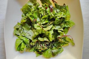 Листья салата помоем, удалим лишнюю влагу. Затем нарвём листья салата на небольшие кусочки.