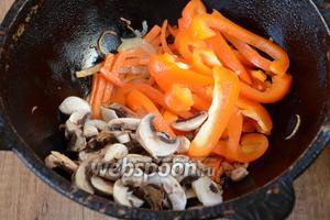 Затем добавляем перец и шампиньоны в казан к моркови и луку. Перемешиваем и тушим около 5 минут на среднем огне.