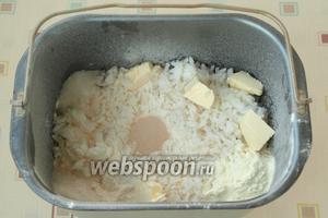 В уголки насыпать сахар, соль и сухое молоко. Нарезать кусочки сливочного масла и разложить сверху риса. По центру сделать углубление и всыпать дрожжи.