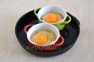 Поставьте кокотницы в сковороду, наполненную водой и отправьте в разогретую духовку.