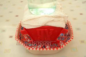 Свисающие концы марли завернуть наверх, накрыть тарелкой и поставить сверху банку с водой или другой подходящий груз. Эту конструкцию убрать в холодильник не меньше чем на 12 часов. Периодически сливать сыворотку стекающую в тарелку.