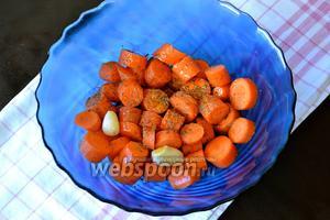 Морковь очистить и нарезать кружочками. Сложить в миску, добавить оливковое масло, прованские травы и зубчики чеснока. Всё хорошо перемешать, чтобы специи распределились по морковке.