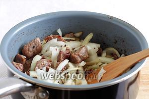 В сотейнике разогреть растительное масло и обжарить кусочки говядины до румяного цвета. Затем добавить лук и слегка подсолить. Помешивая, обжарить все вместе до мягкости лука.