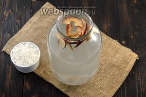 В банку с соком добавить сахар, сушёные яблоки и изюм.
