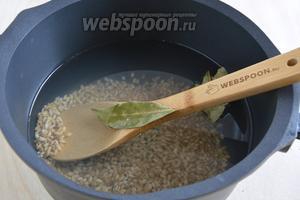 Промойте перловую крупу, засыпьте её в кипящую воду. Добавьте лавровый лист, посолите и варите минут 15 на среднем огне.