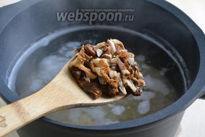 По истечении 15 минут после закипания воды, добавьте к перловке нарезанные на кусочки грибы и грибную воду. Варите ещё 10 минут.