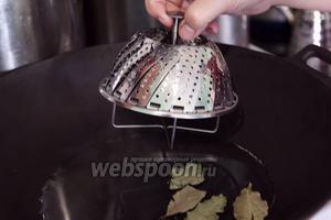 Разогреваем в воке воду с лавровым листом и ставим в него пароварку.