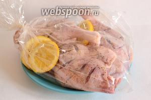 Через 30 минут сложить ножки и лимон в пакет. Пакет завязать и сделать небольшой прокол в верхней части пакета. Положить пакет на противень или в жаропрочную посуду и выпекать при температуре 200°С 40 минут. Затем пакет разрезать и печь ещё 15-20 минут. Так получится золотистая корочка на ножках.