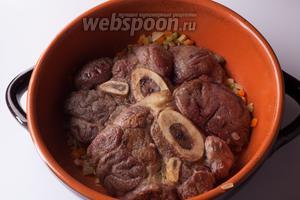 Помещаем шайбы оссобуко поверх обжаренных овощей. Ставим духовку на разогрев на 175°С, а сковороду из-под мяса деглазируем вином и бульоном.