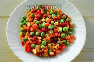 Замороженную смесь овощей выкладываем на тарелку и оставляем на столе для деликатного размораживания. В эту смесь входят перец болгарский, зелёный горошек, кукуруза, морковь, фасоль. Набор овощей может быть самым разным.
