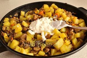 Через минуту добавить картофель, перемешать. Жарить на среднем огне минут 7-10, помешивая. В конце добавить сметану, посолить ещё немного, перемешать и готовить ещё минуты 2. Снять с огня.