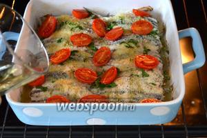 Через 15 минут достаньте форму и залейте рыбу белым винным уксусом. После чего поставьте кильки снова в духовку ещё буквально на 5 минут, чтобы испарился уксус.