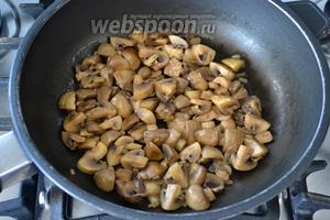 Как только лук посветлеет, добавить к нему грибы. Обжаривать примерно 7 минут, пока выделившаяся от грибов жидкость не начнёт испаряться.