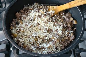 Выложить рис (предварительно не промывать!) и как следует перемешать с мясом, грибами и луком. Позволить рису напитаться всеми ароматами. Через 2 минуты добавить белое сухое вино и позволить ему выпариться.