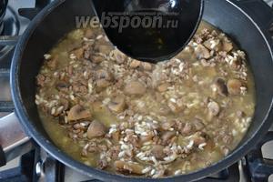 Уменьшить огонь и начать добавлять горячий бульон. Первый раз добавляем бульона ровно столько, чтобы он чуть-чуть прикрывал рис. Затем добавляем понемногу горячего бульона, в процессе приготовления, по мере необходимости. Готовить ризотто до готовности, около 15-17 минут.