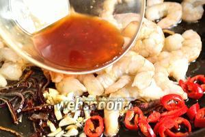 Теперь добавить перец чили чеснок, креветки и заправку. Жарим креветки минуты 2-5 (зависит от размера креветок), пока креветки не станут розовыми.