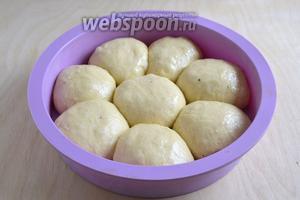 Тесто довольно липкое, смажьте руки маслом и сформируйте из теста булочки. Выложите в форму.