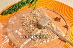 Займёмся ореховой шубой. Орехи нужно измельчить любым способом, но не слишком мелко. Довольно удобно положить орехи в пакет и отбить их молотком для отбивания мяса.