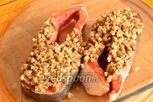 Стейки из рыбы положить в жаропрочную посуду. На рыбу сверху толстым слоем выложить ореховую массу. И поставить запекаться в разогретую до 200°С духовку примерно на 20 минут.