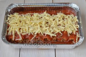 Укройте каннеллони ещё 1 слоем соуса и посыпьте крупно натёртым сыром.