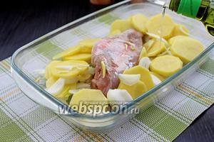 Выложить картофель с луком вокруг рыбы, посолить и поперчить. Полить примерно 1/2 оливкового масла.