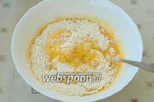 Просеять в миску муку с разрыхлителем, добавить цедру лимона и аккуратно перемешать ложкой.