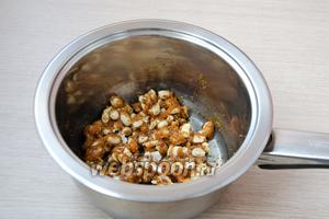 Когда сахар растопится, отправить в карамель очищенный арахис и хорошенько перемешать его, так, чтобы он полностью был покрыт карамелью.
