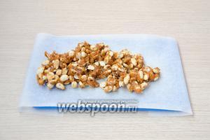 Затем арахис в карамели выложить на пергамент, разровнять его и остудить до комнатной температуры.