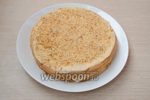 На нижний корж вылить крем и присыпать сверху арахисовым пралине. Проделать то же самое и со вторым коржом.