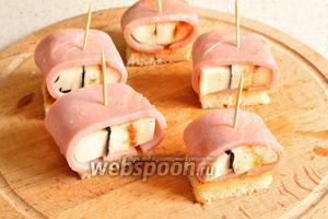 Заворачиваем каждый кусочек фаршированного сыра в полоски ветчины так, чтобы был виден срез на сыре. Каждый рулетик положить на жареный кусочек хлеба и наколоть шпажкой или зубочисткой. Канапе с ветчиной и Моцареллой готовы.
