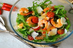 В салатник положите вымытую и просушенную рукколу, помидоры черри, сверху разложите креветки и добавьте Пармезан. Сбрызните всё ароматным маслом из сковороды, в котором обжаривались креветки, и несколькими каплями бальзамического уксуса. Подавайте сразу же!