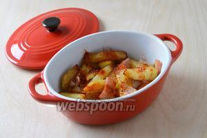 Выложите в кокотницы картофель с грудинкой. Посолите, поперчите, посыпьте паприкой.