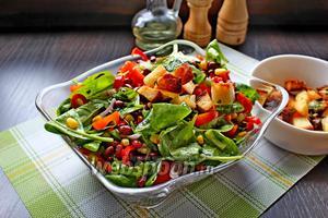 Соединить все ингредиенты (листья шпината, помидоры, лук, перец, фасоль отварную и консервированную кукурузу), перемешать и заправить оливковым маслом. Подавать с чесночным крутонами.