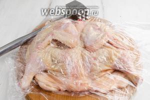 Перевернуть тушку цыплёнка. Снова накрыть её пленкой и легко отбить с другой стороны.
