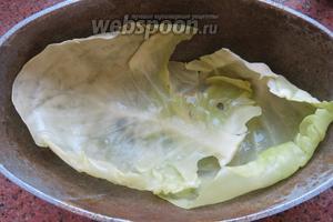 В форму наливаем немного масла и выкладываем дно листьями капусты.