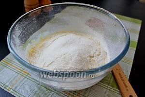 Добавить 50 г (25 г отложить) растопленного сливочного масла и всыпать просеянную муку.