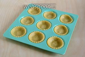 Выложите заготовки в формочки для маленьких тарталеток и выпекайте в заранее разогретой до 200°С духовке около 10-12 минут.