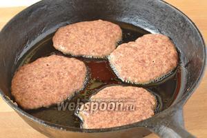 Фарш выложить ложкой на горячую сковороду и жарить на медленном огне под крышкой с одной, а после и второй стороны.