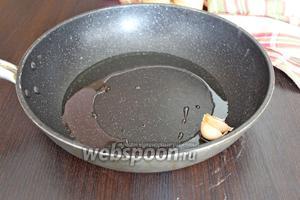 Протереть сковороду чистой салфеткой, налить оставшиеся 50 мл масла, выложить чеснок, обжарить его 1 минуту и выбросить, он отдал все свои ароматы маслу.